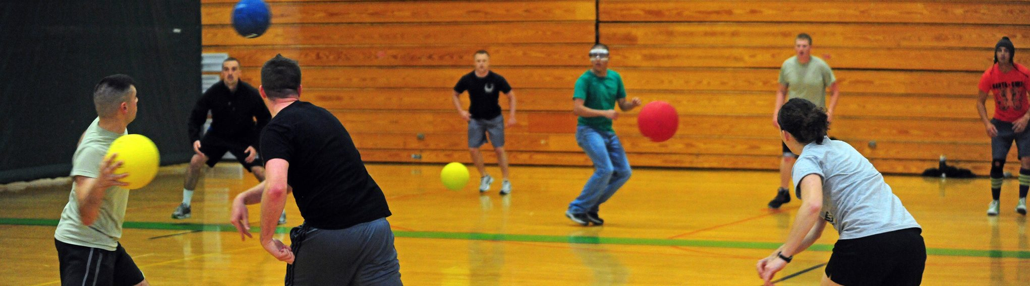 People playing dodgeball with man with blackshirt making a throw