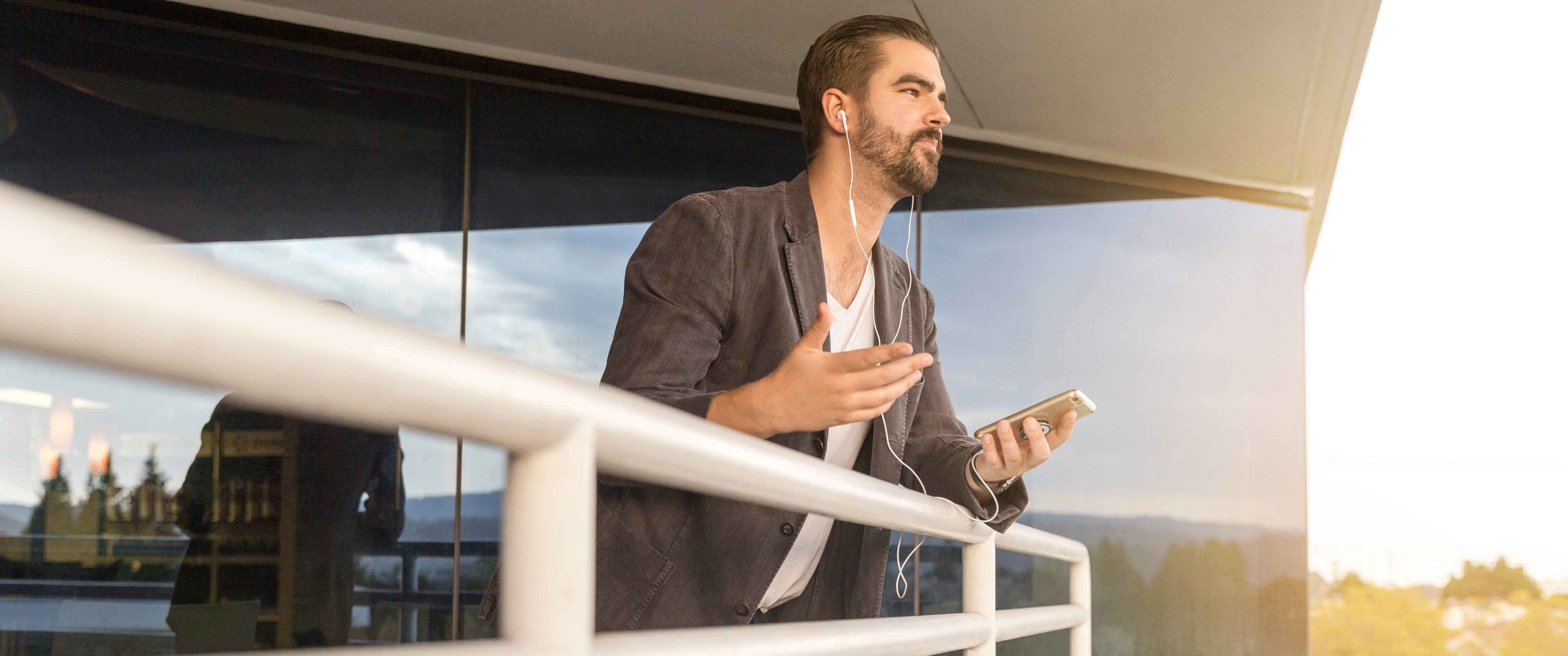 Man with sport jacket talking on iPhone with headset over a railing
