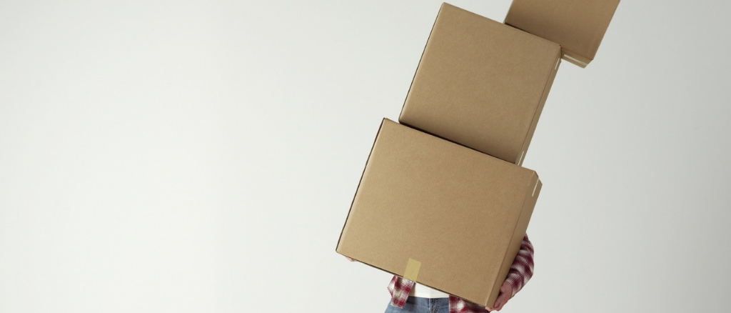 Man lifting 3 boxes and slanting sideways, technology for charities can help do the heavy lifting